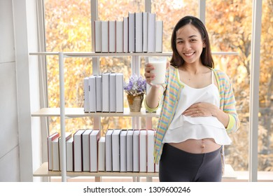 young asian healthy pregnant belly smile while holding a glass of milk (health care concept)