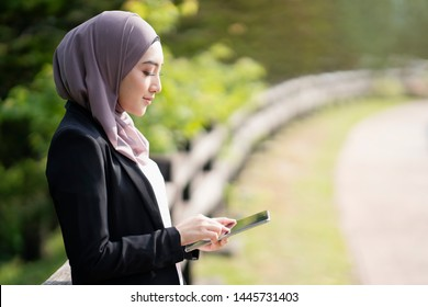 Young Asian Hijab Business Women using cellphone at outdoor.
