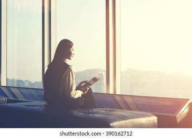 Young Asian hipster girl is holding touch pad, while is sitting in modern interior against window with city view. Businesswoman is waiting her fly in airport and thinking about her awaited vacations