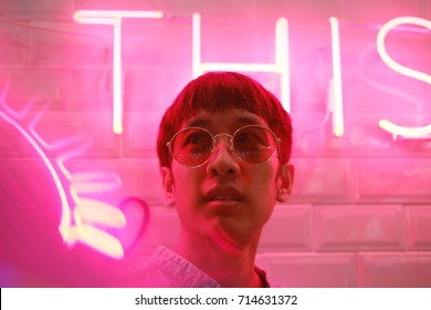 Young asian hipster man in street style fashion concept and wearing sunglasses in pink neon light
