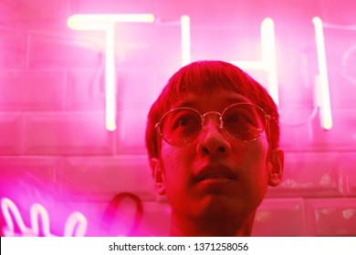Young asian hipster millennial man in street style fashion concept and wearing sunglasses in pink neon light