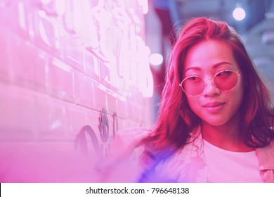 Young asian hipster millennial woman in street style fashion summer concept and wearing sunglasses in pink neon light