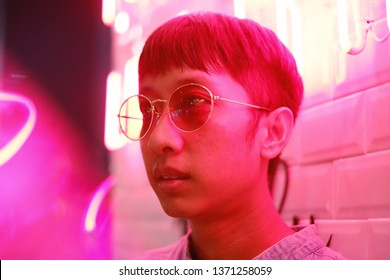 Young asian hipster millennials man in street style fashion concept and wearing sunglasses in pink neon light