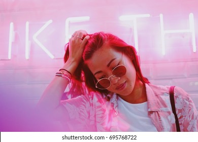 Young asian hipster millennials woman in street style fashion summer concept and wearing sunglasses in pink neon light