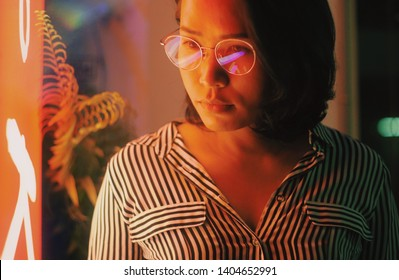 Young asian hipster woman with eyeglasses and neon light in city night light grow