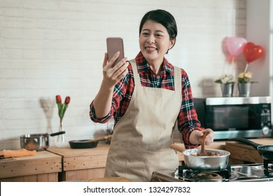 young asian housewife having video phone call on cellphone laughing chatting while cooking handmade chocolate melting in pot on stove stir by wooden spoon in decorated kitchen for valentine day.