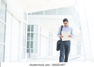Young Asian Indian businessman reading on news paper while walking to office in morning, India male business man, real modern office building as background.