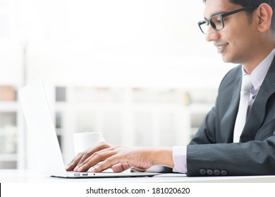 Young Asian Indian businessman using a  laptop  or notebook computer during office break at cafe, relaxing with a cup of coffee. India male business man, real modern office building as background.