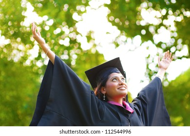 Young Asian Indian female student open arms outdoor on graduation day