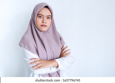 Young Asian Islam woman wearing headscarf is holding hands crossed with serious look. Successful Islam Indonesian woman on gray background.