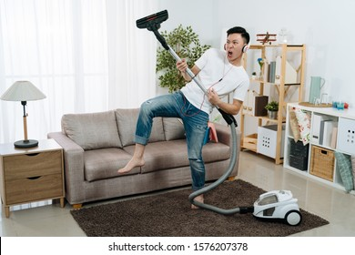 Young asian japanese man having fun during cleaning house. handsome guy relax playing with vacuum cleaner at living room while wearing headphones and dancing with music. male household moving body