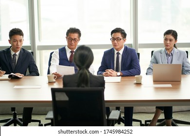 young asian job seeker being interviewed by a group of corporate business executives