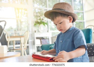 Young Asian kid using a Tablet phone in restaurant with flair light