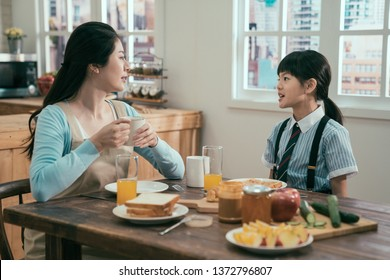 young asian korean mother and daughter having breakfast together in morning at home. mom in apron drinking hot coffee cup talking with cute little girl in school uniform. healthy meal on wooden table