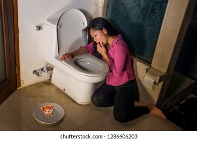 young Asian Korean woman throwing up forcing herself with fingers for vomiting pizza feeling guilty worried about getting fat in bulimia nutrition disorder and weight loss obsession problem