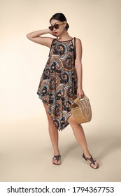 A young Asian lady in sunglasses is wearing leather sandals and loose summer dress with colorful Paisley print. The lady with bamboo handbag put her hand behind head.