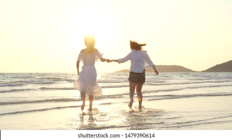 Young Asian lesbian couple running on beach. Beautiful women friends happy relax having fun on beach near sea when sunset in evening. Lifestyle lesbian couple travel on beach concept.