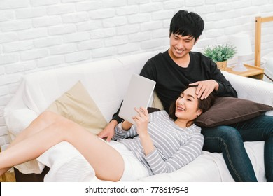 Young Asian lovely couple relax at home, sit on sofa using digital tablet together. Girl lay on man lap. Love relationship, casual domestic life or modern technology lifestyle concept. With copy space