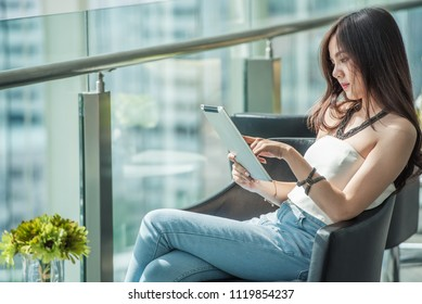 Young Asian lovely creative and working businesswoman holding tablet in relaxing time and working on tablet computer at the new modern style office glasses building, new technology equipment concept.