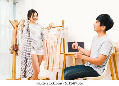 Young Asian lover couple choosing cloth together at home. Girlfriend holding 2 dress, boyfriend thumbs up. Travel or trip prepare, domestic life, married love relationship, or retail shopping concept