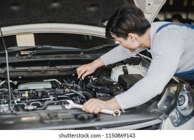 Young Asian machine technicians are analyzing symptoms of broken car at service center repair