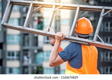 Young Asian maintenance worker man with orange safety helmet and vest carrying aluminium step ladder at construction site. Civil engineering, Architecture builder and building service concepts