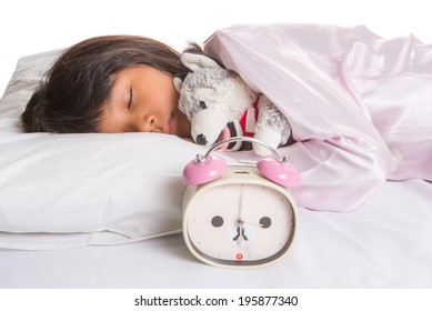 Young Asian Malay girl sleeping peacefully on her bed with an alarm clock