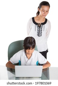Young Asian Malay school girl studying with her laptop with a female teacher observing