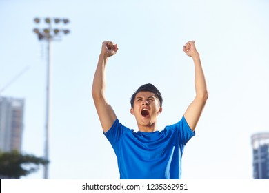young asian male athlete celebrating victory with fists and arms raised
