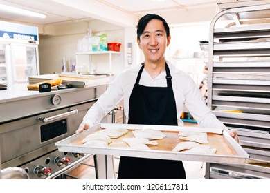 Young Asian male bakery shop chef smiling and looking at the camera while holding a tray of breads in kitchen in bakery shop scene
