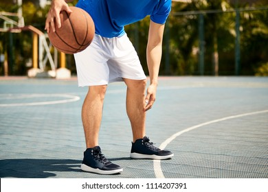young asian male basketball player dribbling and practicing ball handling skill on court.