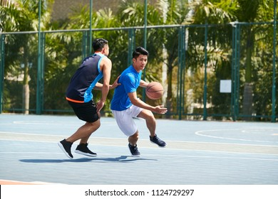 young asian male basketball player playing one-on-one on outdoor court.