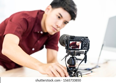 Young asian male blogger setting up camera for recording live vlog video tutorial session at home. IT blogging or vlogging, social media broadcasting or online learning course concept. Focus on camera