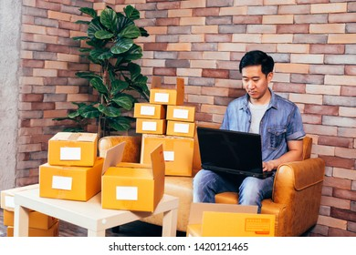 Young Asian male business entrepreneur using computer laptop with parcel boxes to deliver customers from orders - Online business and ecommerce