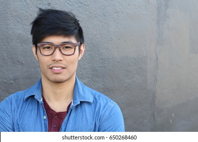 Young Asian male with glasses smiling with copy space