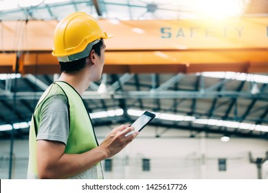 Young Asian male heavy industral worker using a digital tablet inside manufacturing and factory site with crane behind