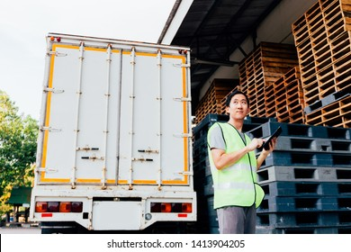 Young Asian male logistics warehouse distribution business entrepreneur wearing reflective jacket using a digital tablet. He is surrounded by plenty of pallets and truck in shipping cargo.