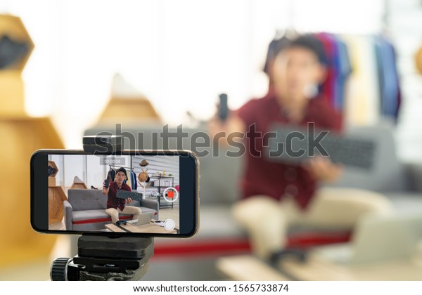 Young asian male online merchant blogger using smart mobile phone to recording live vlog video for review IT product goods. Online influcencer on social media concept. Focus on mobile phone