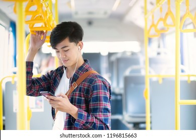 Young asian male passenger using mobile phone on public bus.