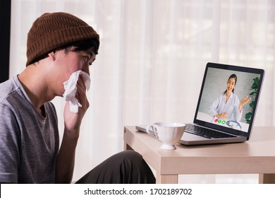 Young Asian male patient with sickness using laptop to video call conferencing with doctor at home. Medical .consultation via internet connection. Telecommunication Healthcare concept.