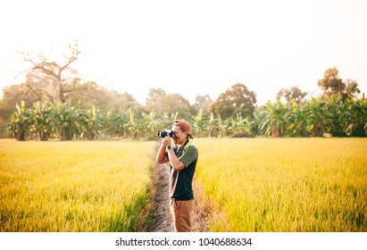 Young asian male photographer in rice field. Travel lifestyle concept in nature forest. Thailand