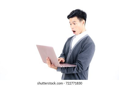 Young Asian male student in grey jacket typing on laptop with surprised expression on his face isolated on white background
