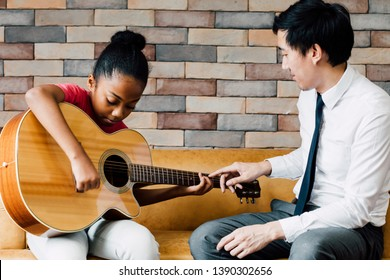 Young Asian male teacher giving a guitar lesson and teaching how to play guitar to African American girl in indoors room