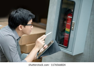 Young Asian male technician checking red fire extinguisher in fire hose cabinet (FHC) by using digital tablet and pen. Building service and maintenance concepts