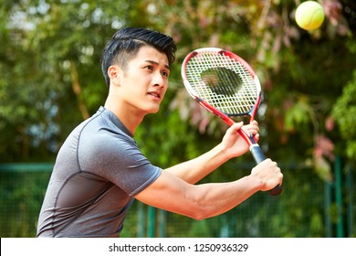 young asian male tennis player hitting ball with a backhand