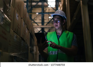 Young Asian male warehouse worker using a digital tablet inside warehouse to check inventory and stock management in factory - storage and factory stocktake management concept