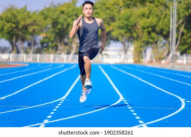 young asian man athlete running and training  on the  track