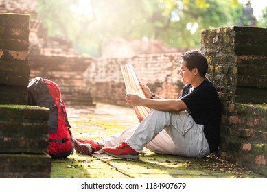 Young asian man backpacker View map landmark archaeological  in Ayutthaya Province, Thailand. Travel concept.