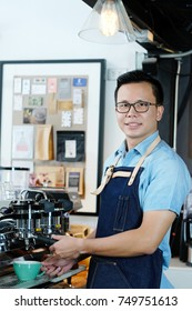 Young asian man barista making a coffee cup at cafe counter background, small business owner, food and drink industry concept