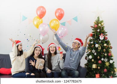 Young Asian man and beautiful Asian woman drink champagne celebration with best friend.Smiling face in room with Christmas tree decoration for holiday festival.Christmas Party and celebration concept.